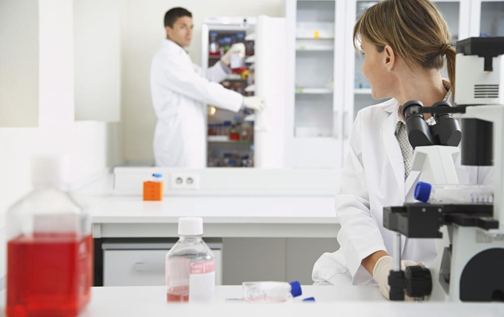 Scientist retrieving pharmaceutical products stored in lab refrigerator
